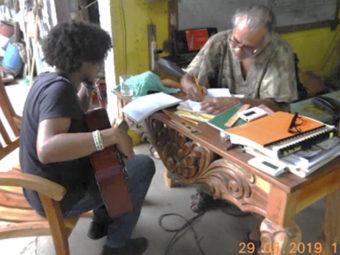 Der Gründer Gerson Vasquez Ruiz erklärt einem Jugendlichen Gitarrengriffe.